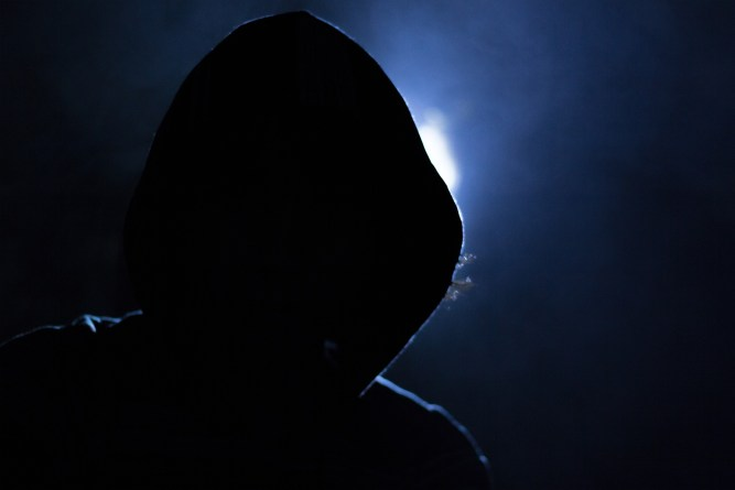 Hooded figure shilouetted in front of a blue light