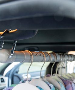 Expandable clothing rod on vehicle grab handles shown with hanging clothes