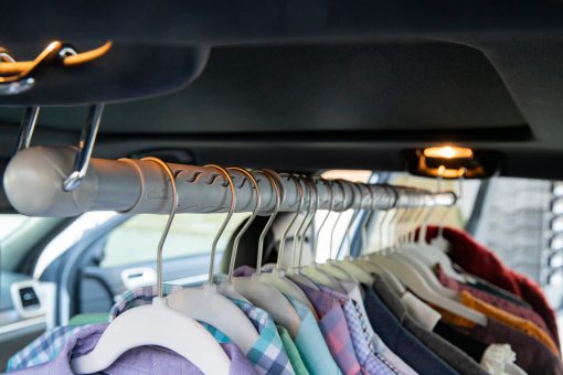 Expandable clothing bar loaded with hanging clothes for moving