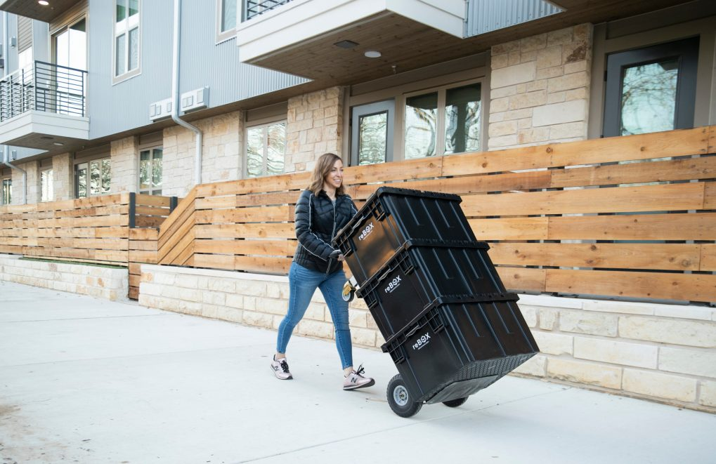 smiling woman pushing reusable moving totes on sidewalk with a dolly