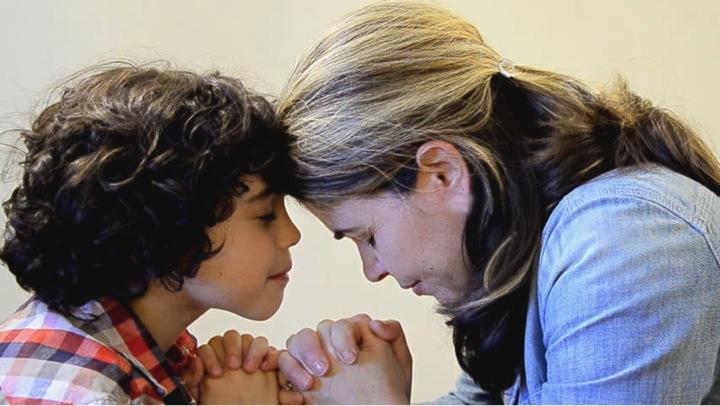 mae orando com o filho