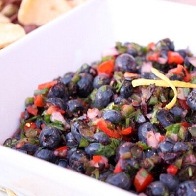 Fresh Blueberry Salsa displayed in a white bowl with chips on the side