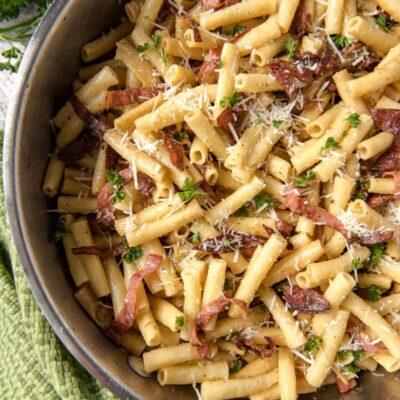 ziti carbonara in a skillet - green cloth napkin and fresh parsley on the side