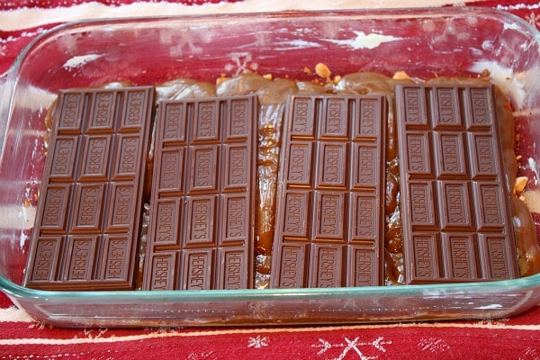 chocolate bars set on top of hot toffee in a baking dish to make almond roca