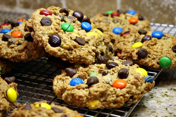monster cookies piled haphazardly on a cooling rack