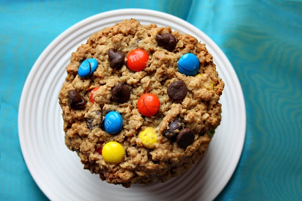 overhead shot of a stack of monster cookies on a white plate with a teal blue background