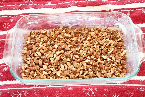 toasted almonds in a baking dish to start the process of making almond roca