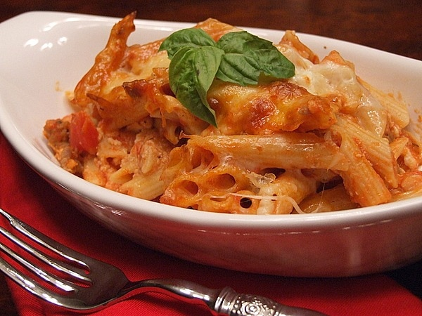 serving of baked penne with Italian sausage in a white dish with fresh basil garnish