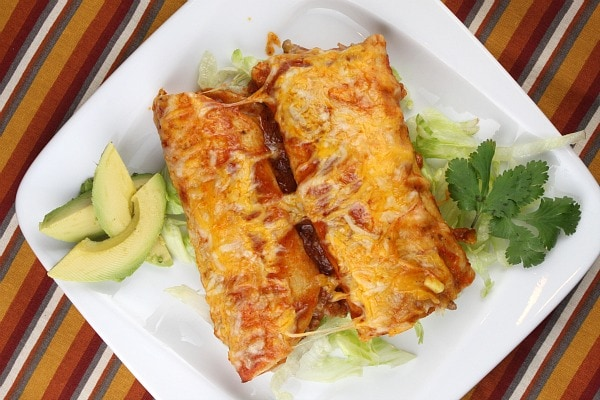 two beef enchiladas on a white plate with avocado and cilantro garnish- set on a striped placemat