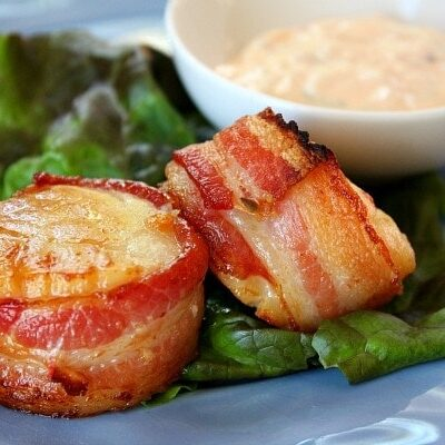 two bacon wrapped scallops on a blue plate garnished with lettuce leaf and served with sauce