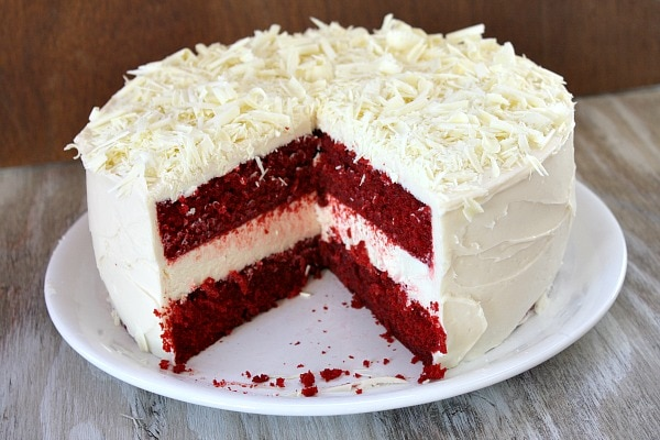 red velvet cheesecake cake sliced open to reveal the inside on a white plate