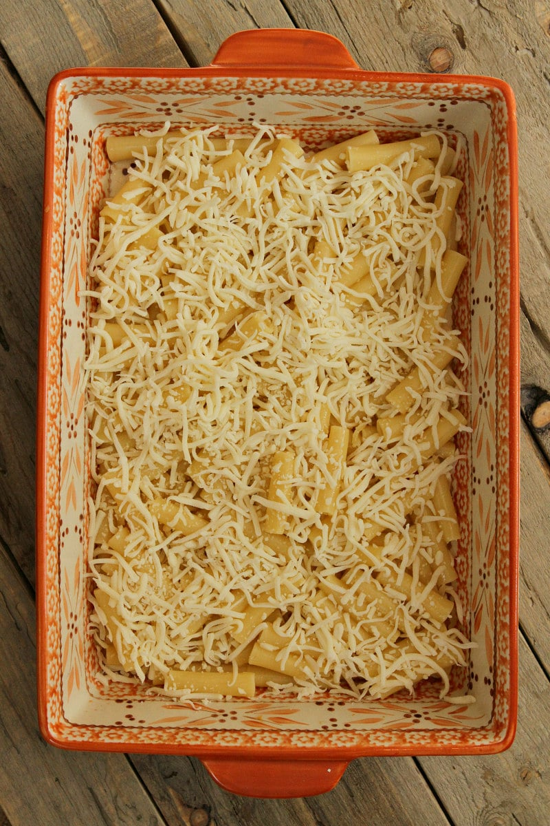 overhead shot of making pastitsio in process looking at noodles and cheese in the casserole dish