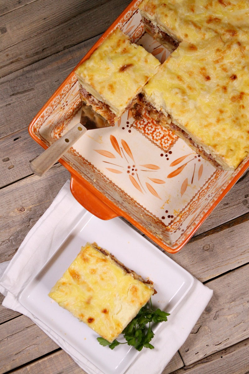 overhead shot of pastitsio in a casserole dish with spatula taking a slice out