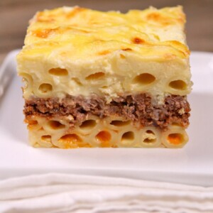 Slice of Pastitsio on a white plate with a white napkin