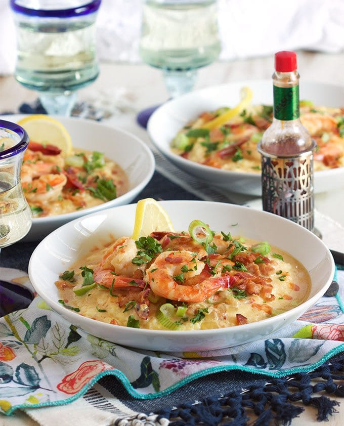 shrimp and grits in three white bowls on a table setting with patterned napkin and a bottle of hot sauce