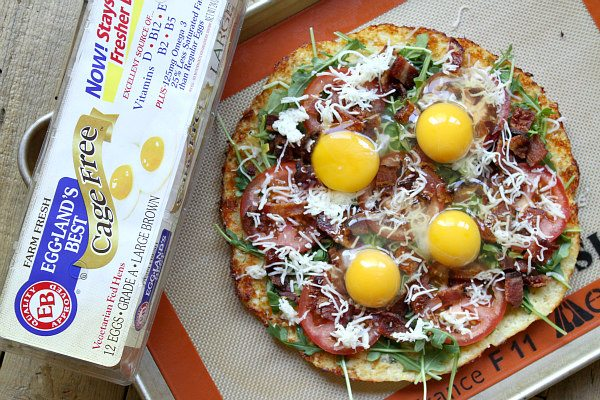 preparing Cauliflower Crust Bacon and Egg Pizza adding eggs