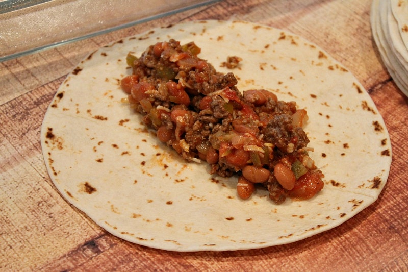a tortilla with beef and bean filling on top of it