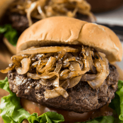 jucy lucy burger piled high with grilled onions