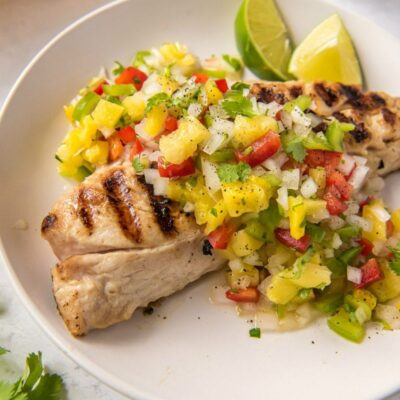 overhead shot of red snapper with pineapple salsa on a white plate with lime garnish