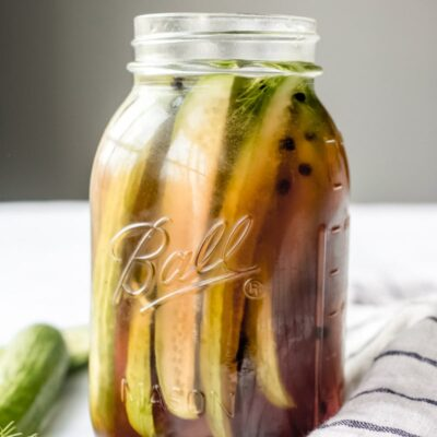 side shot of beer pickles in a tall jar with a blue and white napkin on the side