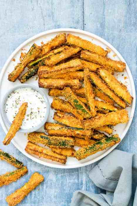 Air Fryer Zucchini Fries served with herbed yogurt dip on a white plate