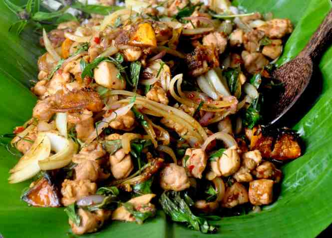 Stir fried chicken with sweet potato, Thai basil and kaffir lime leaves served on a banana leaf with wooden serving spoon