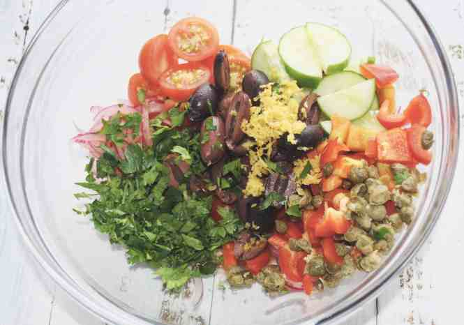 quick tuna and cannelloni bean salad with tomato, cucumber and capsicum added to glass bowl