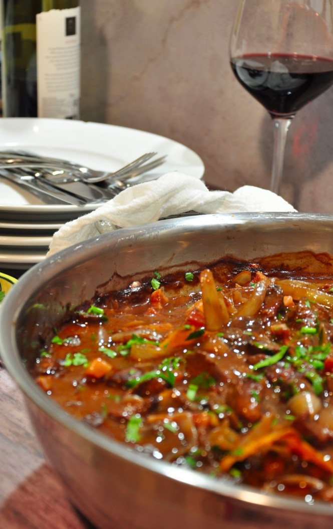 Beef Bourguignon in silver pan with parsley garnish ready for eating