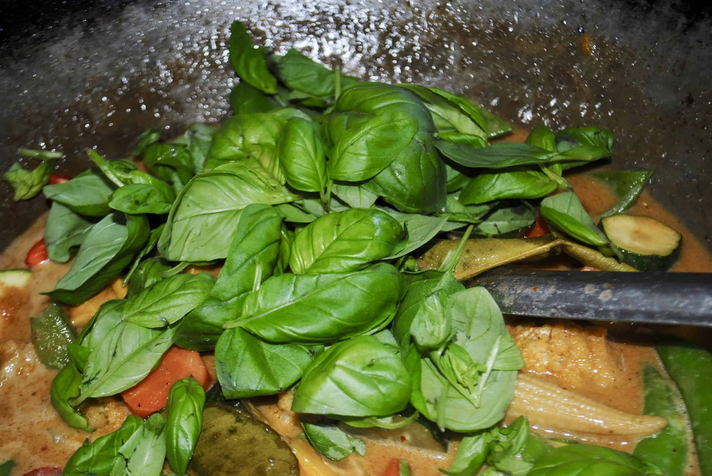 Thai vegetable red curry with basil leaves added at the end of cooking