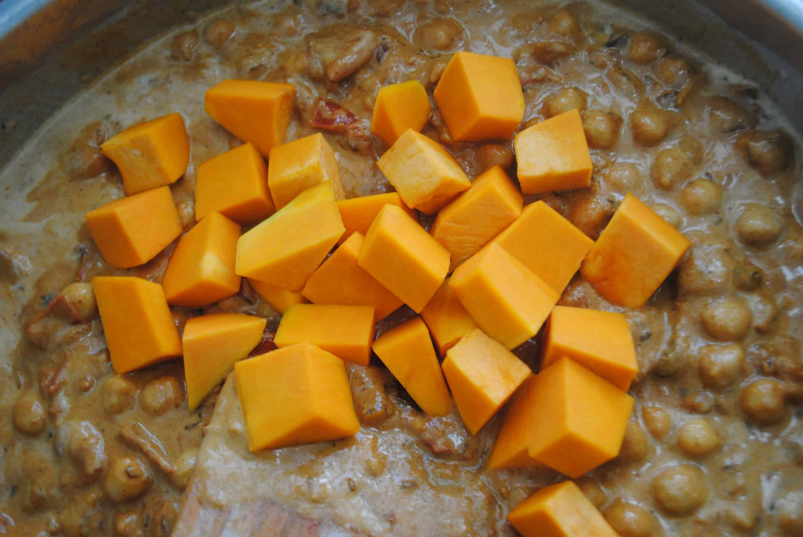 indian vegetable curry adding pumpkin to wok