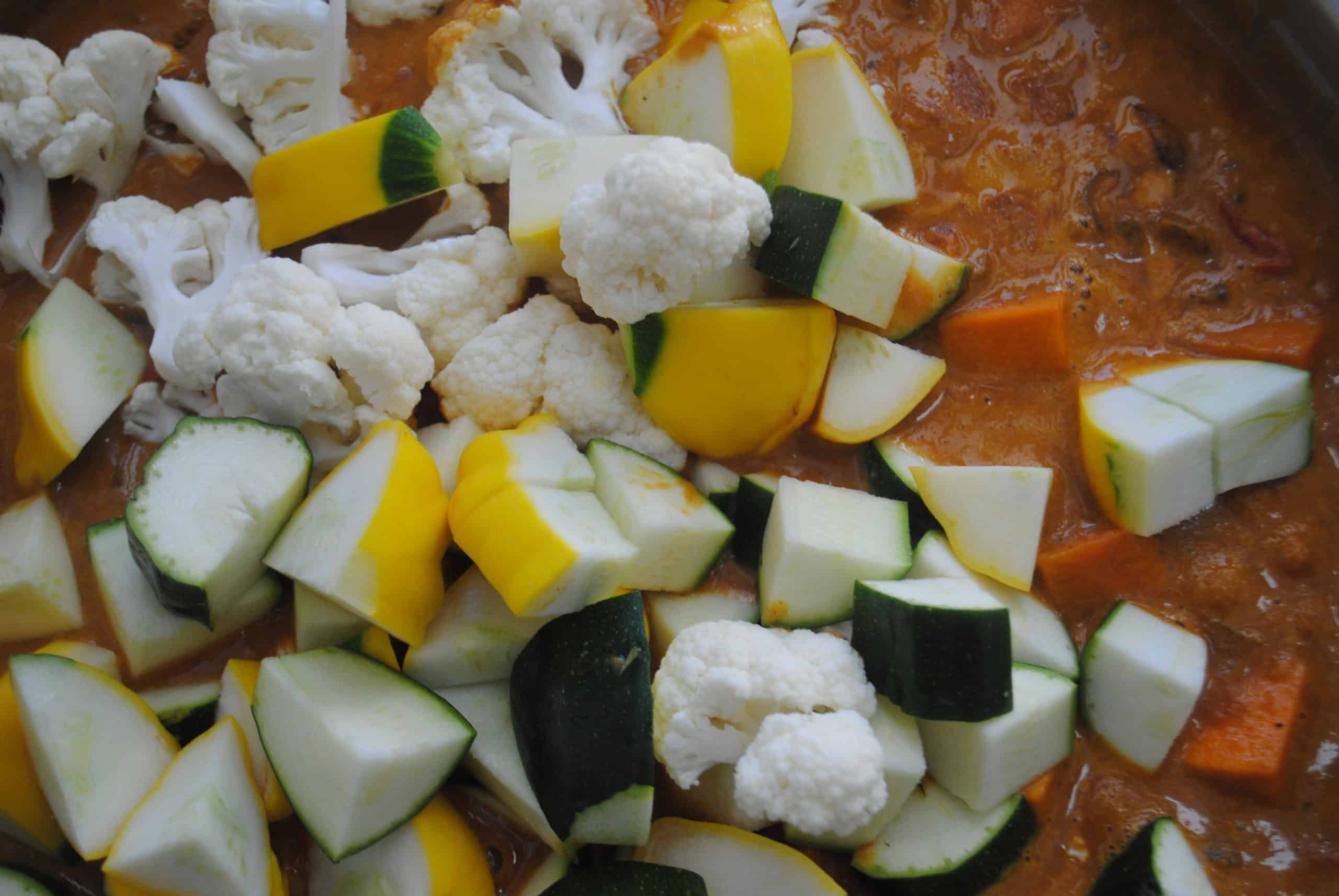 indian vegetable curry adding cauliflower, zucchini and squash to wok