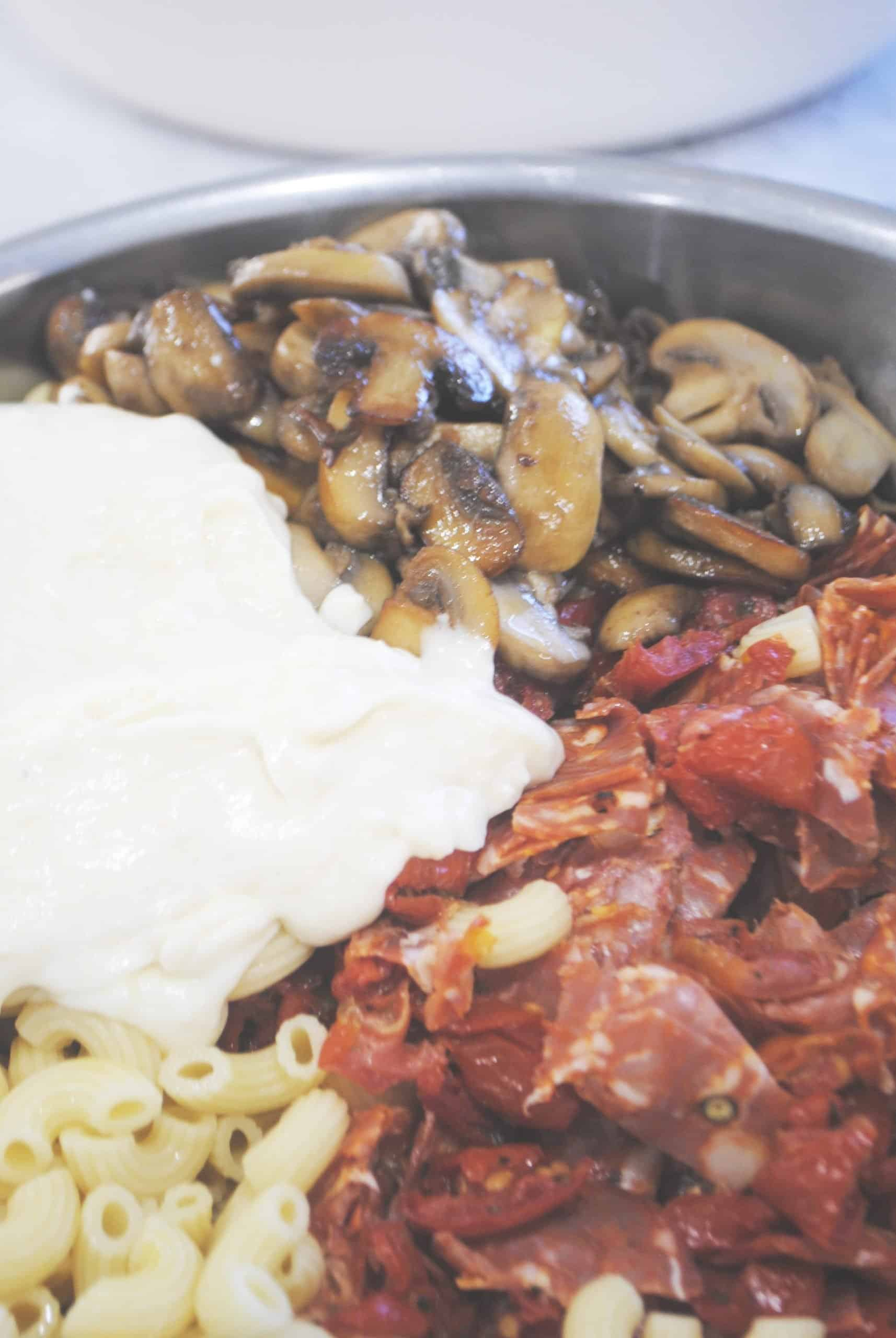 macaroni with salami, tomato and mushroom with all ingredients in bowl ready to mix