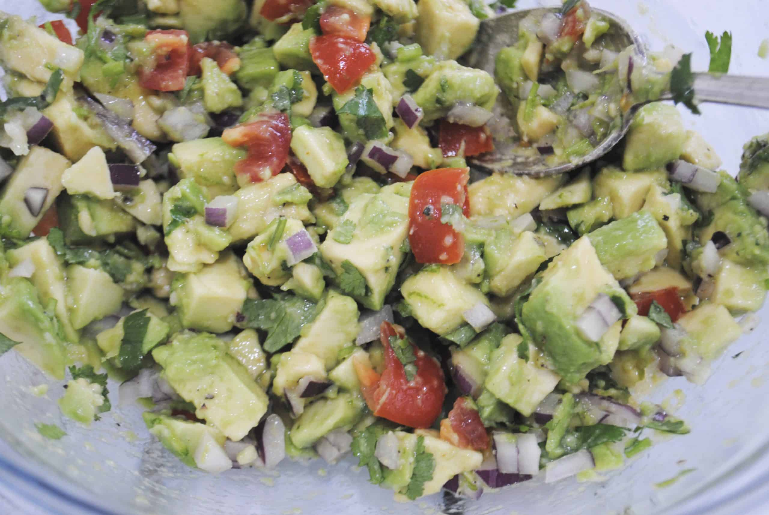 guacamole ingredients added to avocado and lime juice gently mixed together in a glass bowl