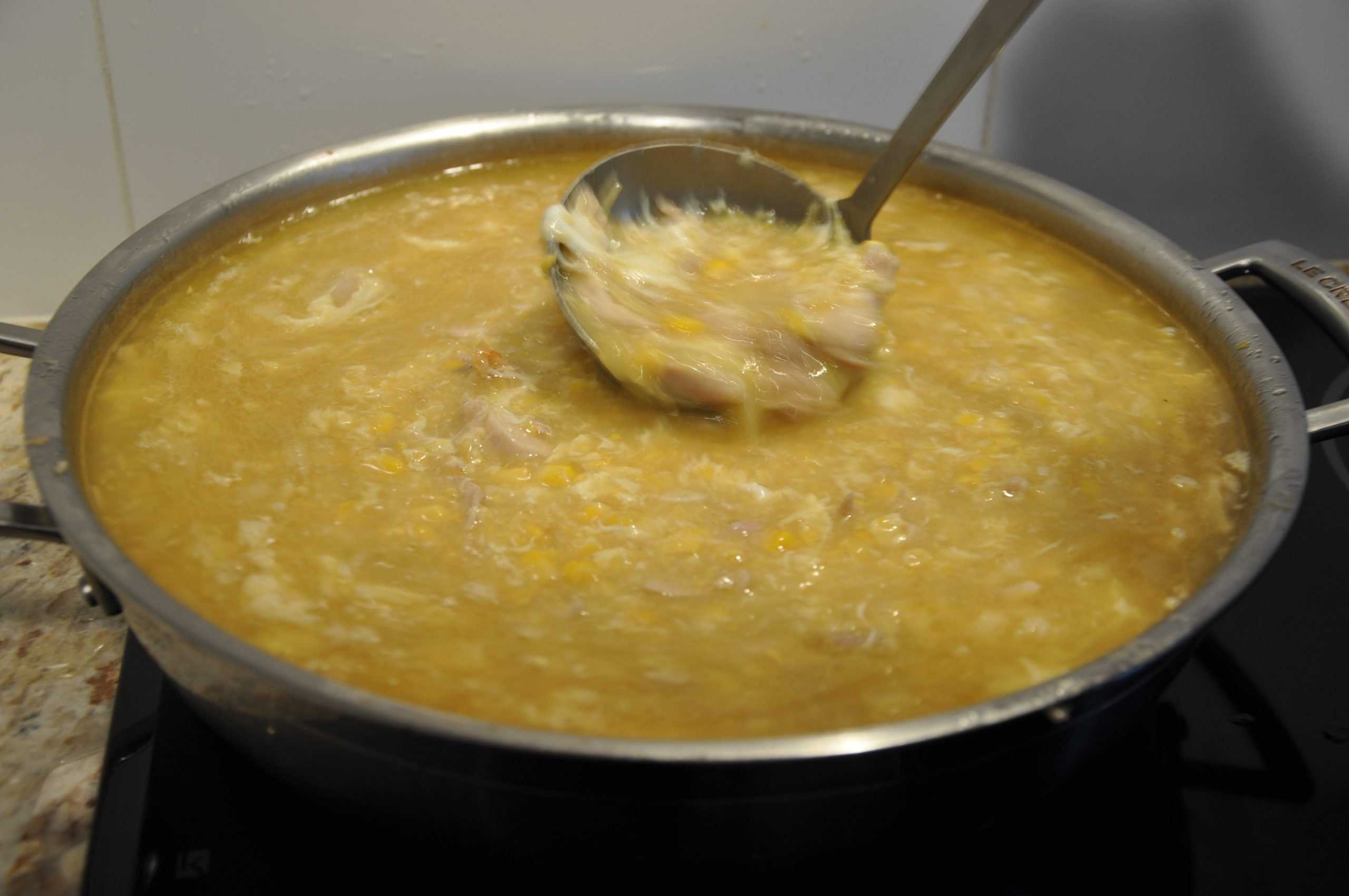 chicken and corn soup stirring whisked eggs into soup with a ladle