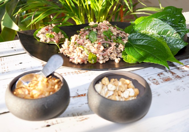 chicken larb cooked and served on a somber plate with betel leaves and 2 bowls with fried shallots and cashew nuts