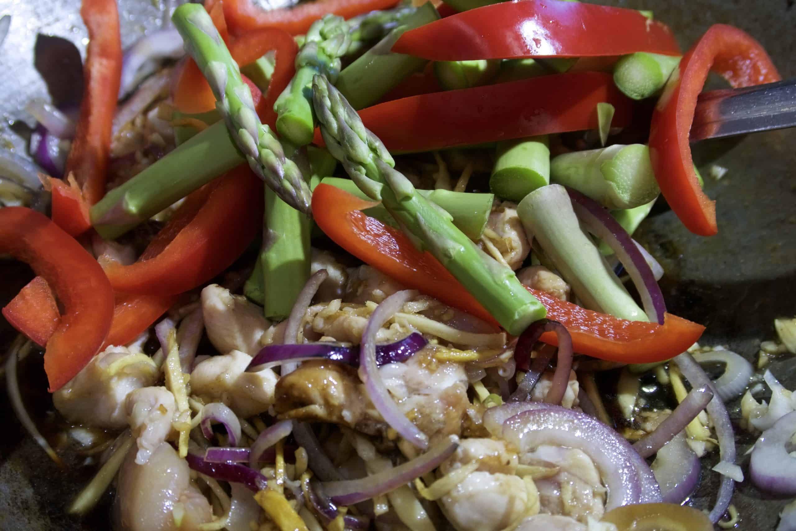 chicken stir fry with asparagus and ginger adding asparagus and capsicum to stir fry in wok