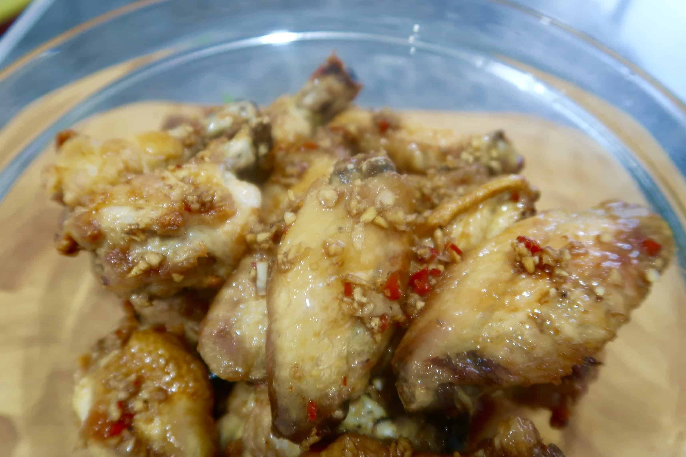 oven baked chicken wings with ginger garlic dressing cooked wings in a glass bowl with dressing