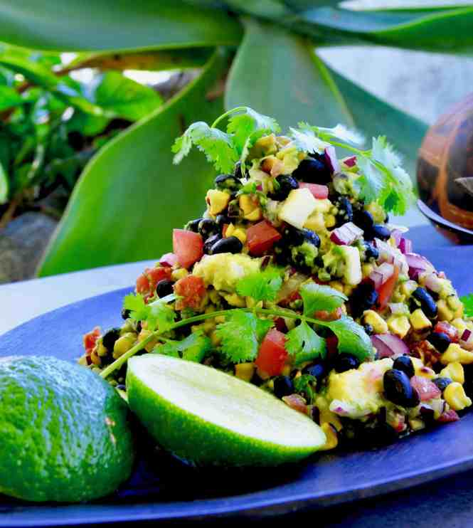 corn salsa with colourful vegetables and a lime cheek served on a platter with a spoon and coriander garnish