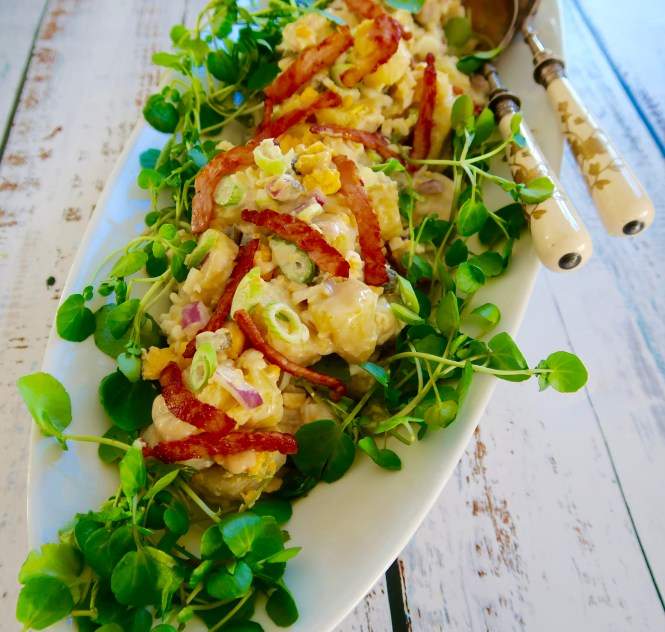 easy egg and bacon potato salad served on a white oval platter with watercress garnish and salad servers