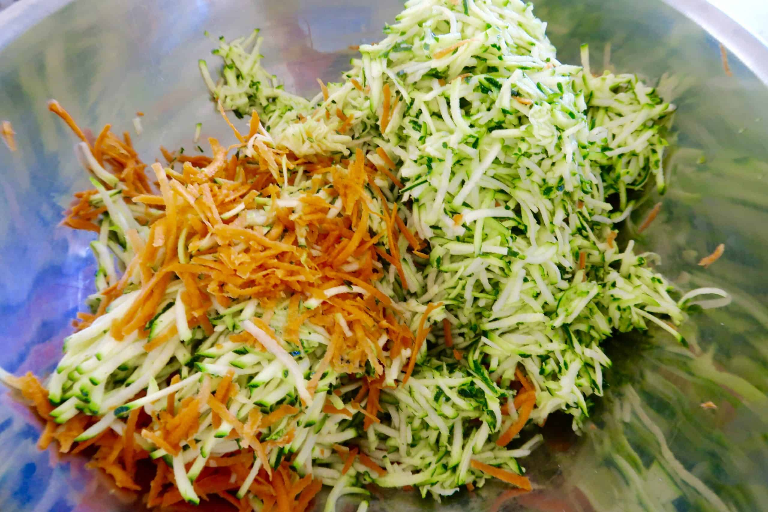 zucchini and bacon slice zucchini and carrot grated in a silver bowl