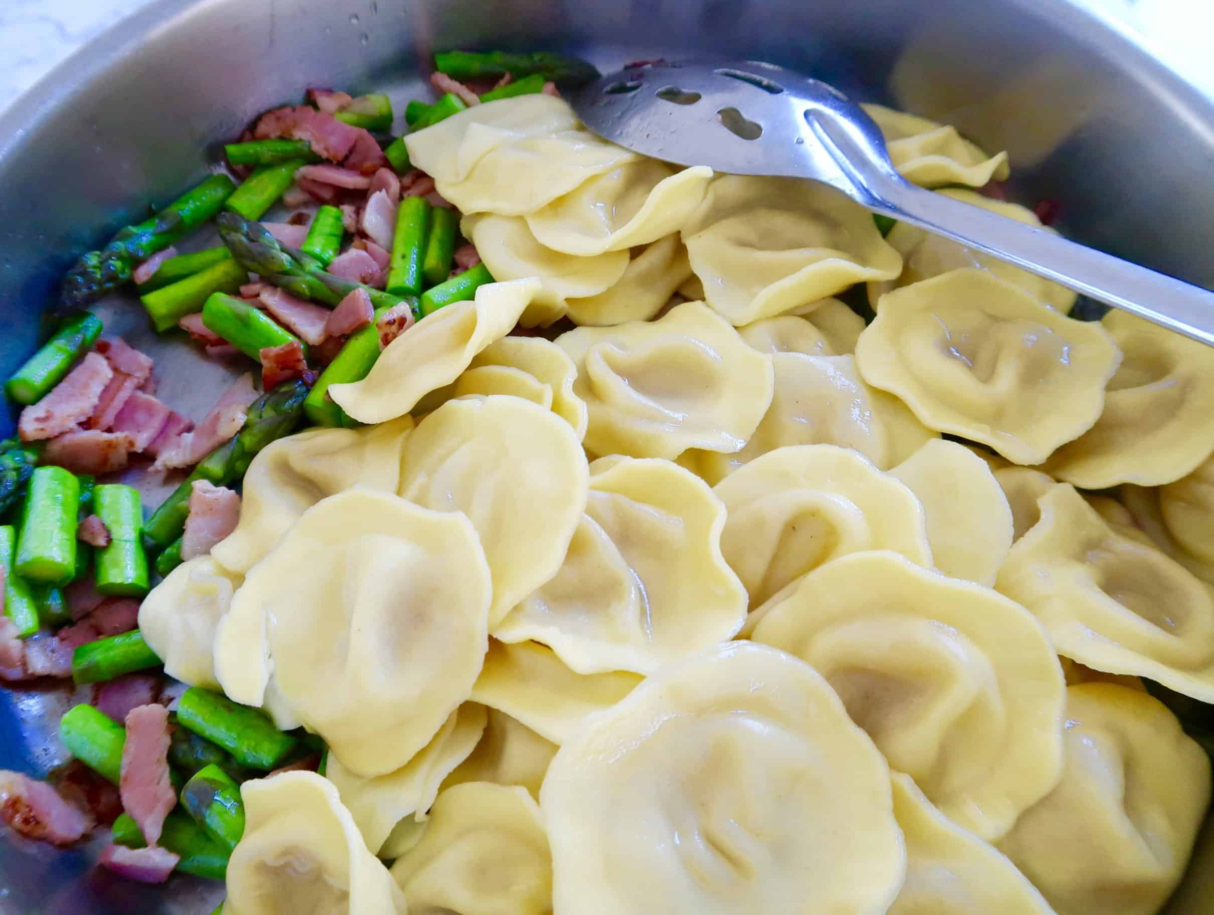ravioli with asparagus and bacon with cooked ravioli added to frypan with asparagus and bacon