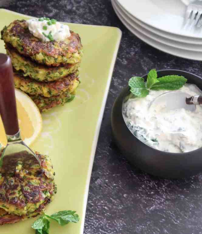 zucchini fritters served on a green rectangular plate and a bowl of yogurt in the fore ground
