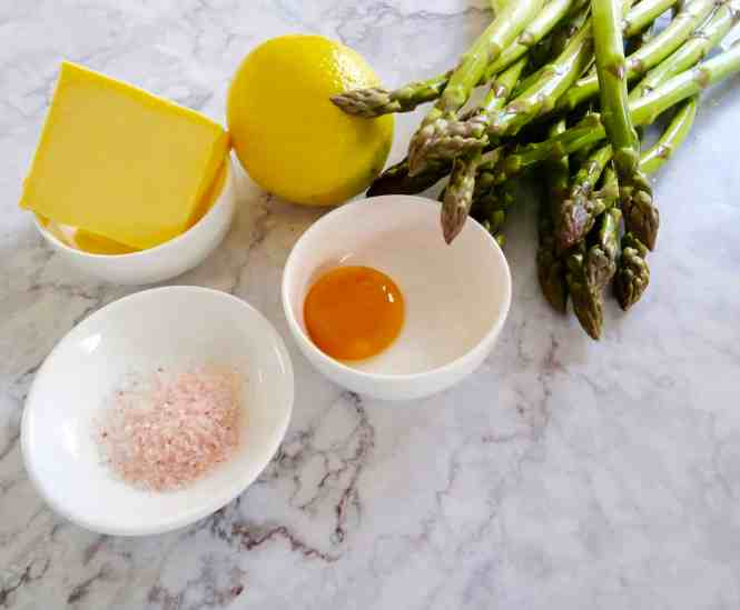 asparagus with hollandaise ingredients on a marble bench