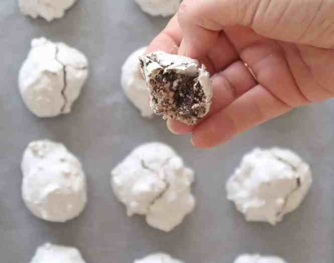 backing tray of cooked forgotten meringue cookies with a hand holding half a cookie