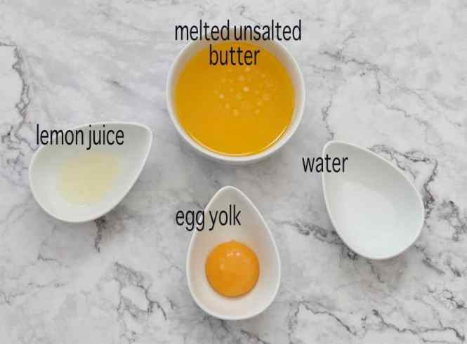 easy hollandaise sauce ingredients on a marble bench
