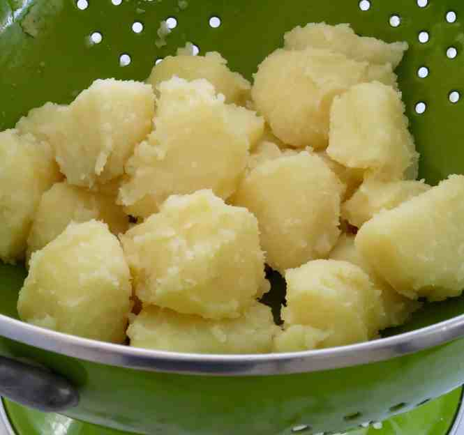 potatoes in a green colander all roughed up after shaking