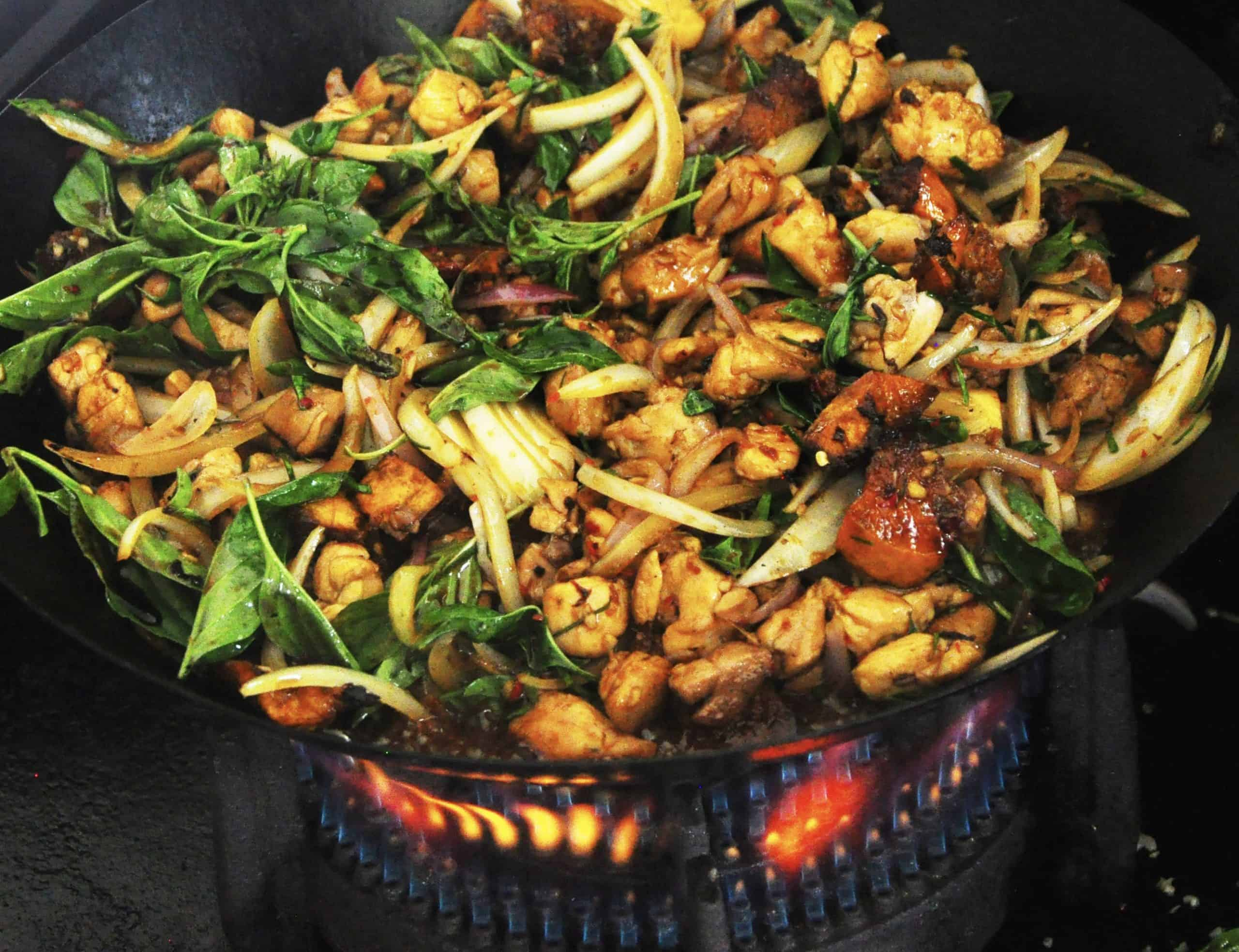 stir fried chicken with sweet potato and kaffir lime cooked in a wok over flames and ready to serve