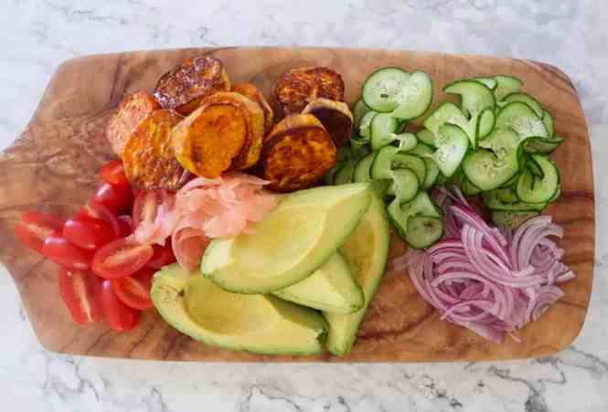 roasted sweet potato, avocado and pickled ginger salad vegetables on a wooden chopping board