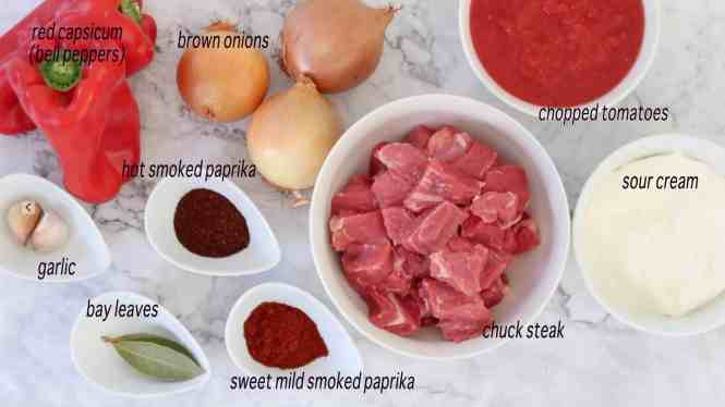 ingredients for Beef Goulash on white bowls on a marble table