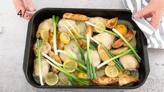 shallots added to a black baking tray to make chicken fennel lemon tray bake